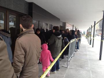 Image: a large group of people in line.